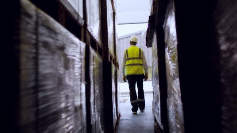 An industrial worker walks through a dark and narrow passageway between two rows of stacked goods in a warehouse before walking out into bright daylight. Shot at a low angle and in slow motion.
