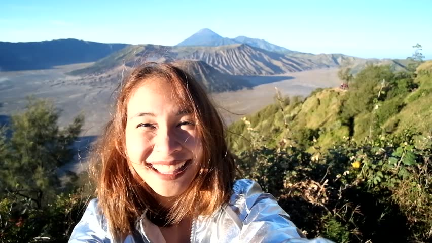 Cheerful enthusiastic Asian tourist girl happily turn around in Bromo Tengger Semeru National Park, East Java, Indonesia. Young woman have fun sightseeing with volcano, desert, and sky. (Selfie shot) #31950964