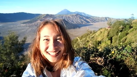 Cheerful enthusiastic Asian tourist girl happily turn around in Bromo Tengger Semeru National Park, East Java, Indonesia. Young woman have fun sightseeing with volcano, desert, and sky. (Selfie shot)