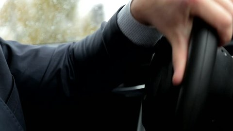 Respectable, responsible man driving car. Raining day. Dangerous road. The man in a suit. Close up. The man holds the steering wheel.