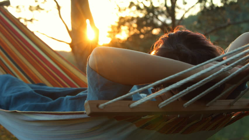 Woman lies in a hammock and enjoys the sunset
