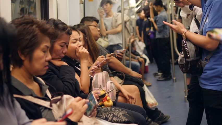 Asian People Using Smart Phones and Gadgets Inside BTS Subway Train Wagon. 4K. Bangkok, Thailand - 21 OCT 2017.