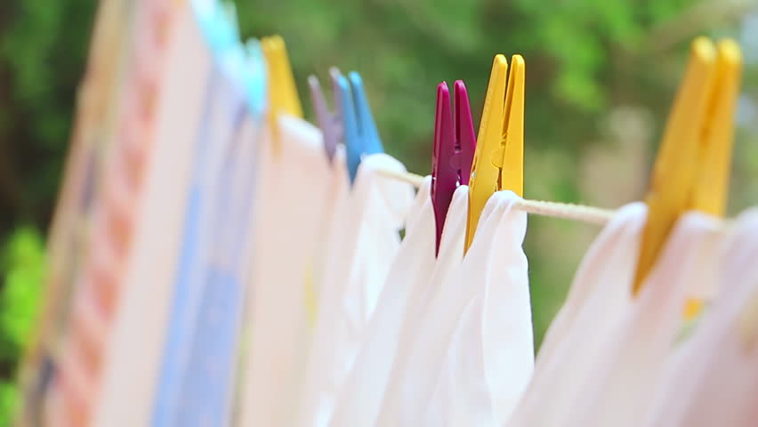 Drying laundry on the clothesline close up. Clean laundry hanging on a clothesline. Clean washed laundry hooked with clothespin hanging to the on clothesline