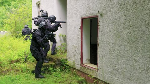 Four Special Force Soldiers run in front of a bedraggled building.