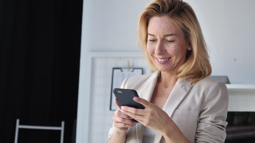 Portrait adult elegant woman using smartphone indoors.Smiling businesswoman wearing suit holding smart phone. Lady chatting in social media or use web application or shopping online. Happy cheerful