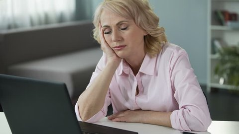 Mature woman falling asleep at workplace, lack of vitamins and energy, tired