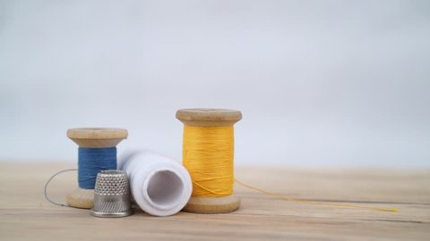 Still image of old spool of thread with needle and sewing thimble. Sewing background. Tailor's work table.