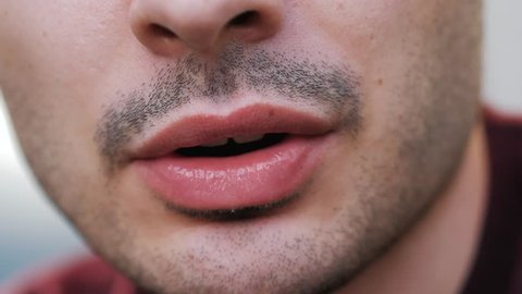Close up on the mouth of a young man talking to the camera