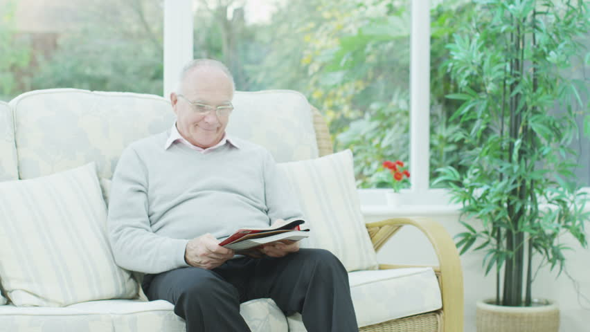 A senior couple are relaxing at home in their conservatory and they receive a happy letter from their loved ones.