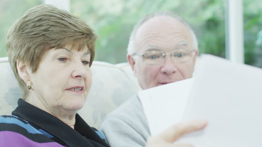 Portrait of a senior couple who are concerned about their financial affairs. They are sitting in their conservatory at home and looking through some documents. In slow motion.