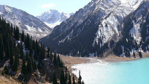 Tilt down of the emerald Big Almaty Lake in autumn season.
