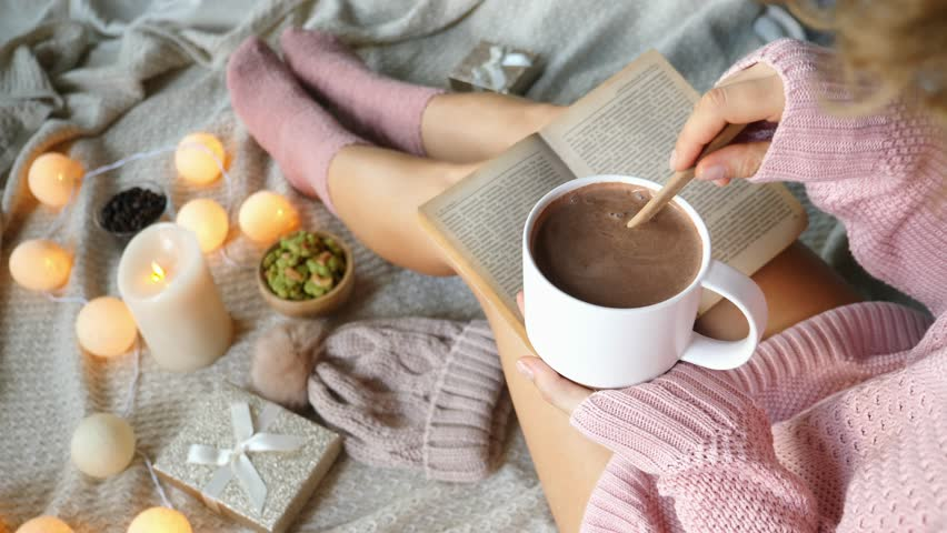 Hipster Girl Reading Book With Hot Drink In Comfortable Cozy Sweater. 4K.