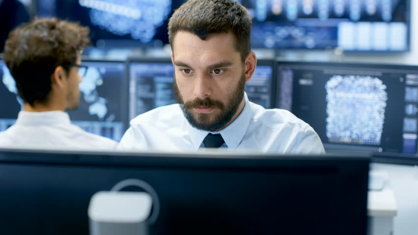 Neural Network and Machine Learning Engineer Programming at His Workstation. Office is Crowded With People Working. Multiple Displays Show Neural Network, Artificial Intelligence Representation. | Shutterstock HD Video #32060674