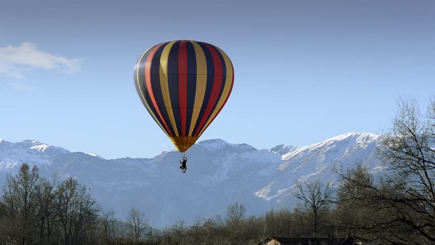 hot air balloon in flight over mountains