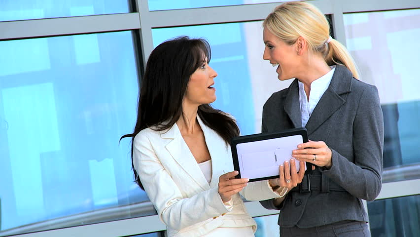 Two smart female city businesswomen outside a modern office building using a wireless tablet | Shutterstock HD Video #3206734