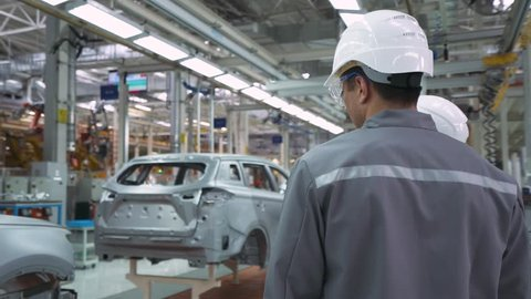 Automobile plant, modern production of cars, man and woman engineers discuss car production, assembly line of cars.