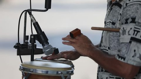 Street musician playing conga drums on the beach.