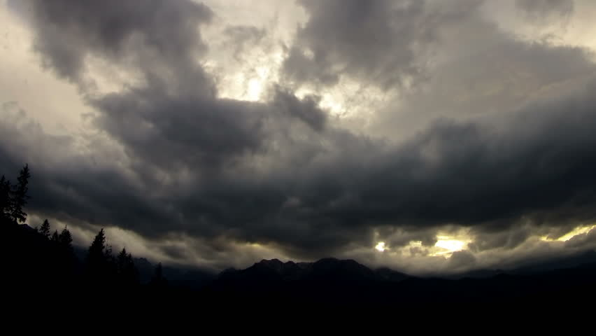 Time lapse of dark clouds over the mountain.