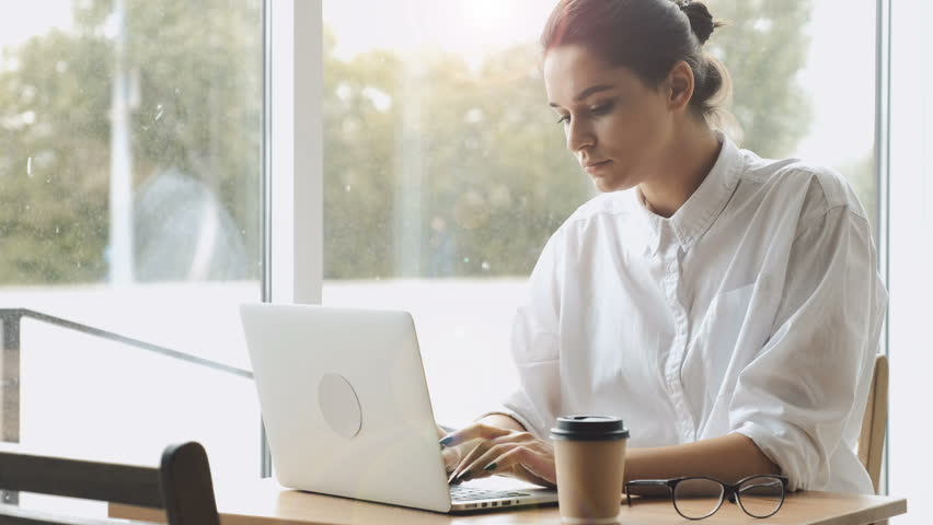 Young serious woman working on laptop at cafe | Shutterstock HD Video #32109004