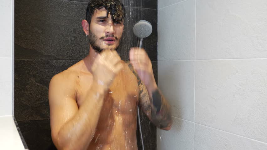 Muscly guy in tats showering