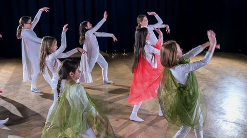 Girls in tight white costumes and green capes are dancing on stage and are performing in a school play.