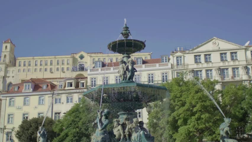 Detail of the fountain splashing in Rossio Square or Praca Dom Pedro IV in Lisbon with typical building in background, Portugal, Europe. | Shutterstock HD Video #32134504