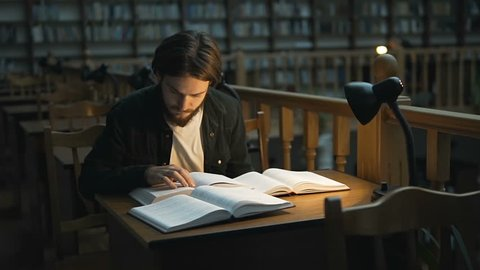 Young student reading in a library hall on table with lot of books and lamp, indoor dusk slowmotion