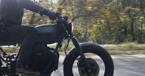 A guy in a black leather jacket and helmet riding a classic motorcycle on a forest road. Close-up on the side