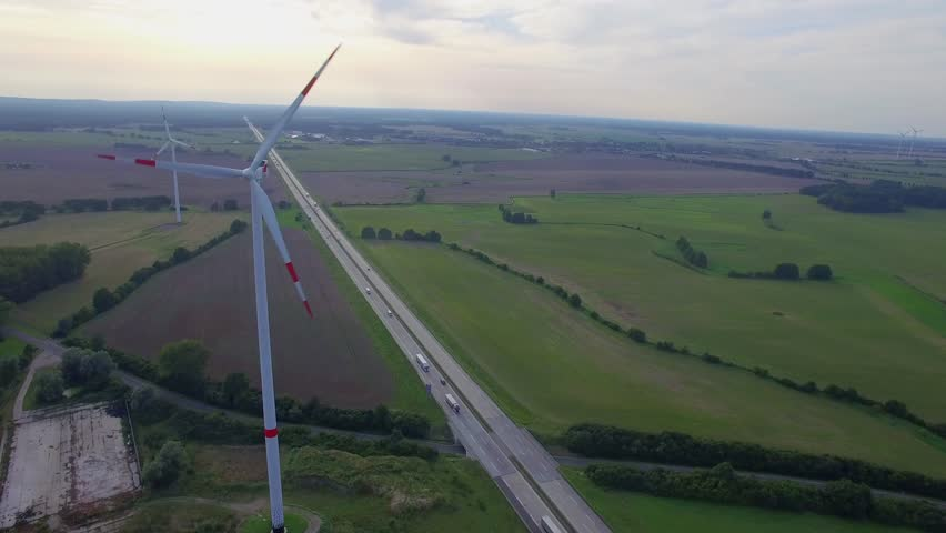 Fly close to wind turbine propellers spinning above road aerial 4k. Wind farm power station in Europe produce renewable sustainable energy in distance from car truck lorries move countryside highway