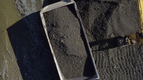 Aerial view, hydraulic scoop of excavator close up excavate sand and loading tipper truck, camera motion to trailer
