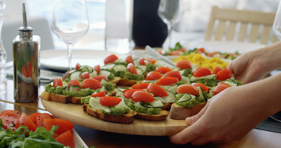 Waiter Serves Beautiful Organic Avocado Sandwiches/ Bruschetta on a Wooden Tray, Table Furnished in Mediterranean Food: Seasonal Vegetables, Olive Oil. Shot on RED Epic 4K UHD Camera.