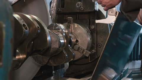 Close up of man hands checking micrometer reading after grinding crankshaft