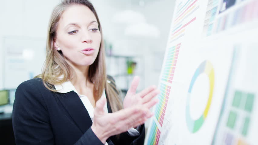 Close up of an attractive female professional in business dress giving a presentation to her colleagues. In slow motion.