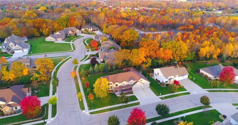 Tranquil idyllic neighborhood amid colorful Autumn trees at dawn, aerial view.