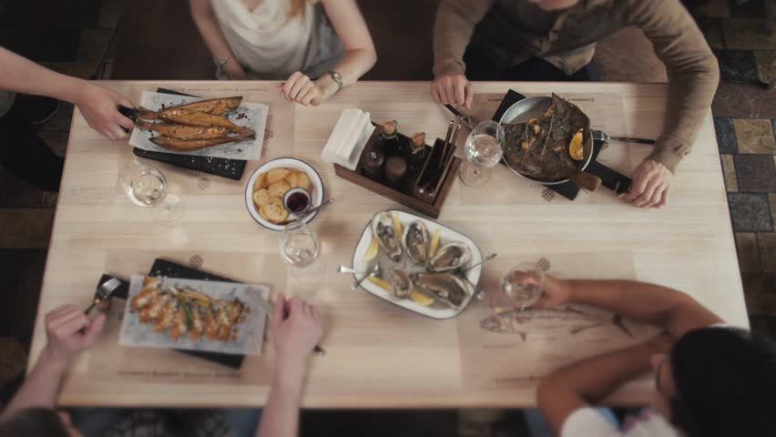 Food Table Healthy Delicious Organic Meal Concept. Enjoying dinner with friends. Top view of group of people having dinner togetherwith fish seafood oysters wine dorado and salad