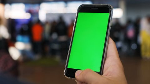Man male traveler holding using mobile smart phone modern tech waiting ready board blurred people background airport floor searching information foreign local flight green screen chromakey chroma key