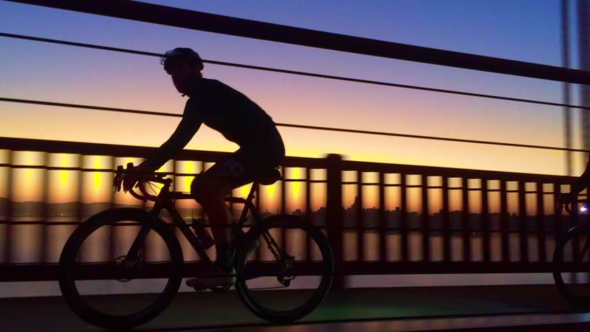 A silhouette of a cyclist riding his bike across the Golden Gate Bridge during the morning sunrise over downtown San Francisco