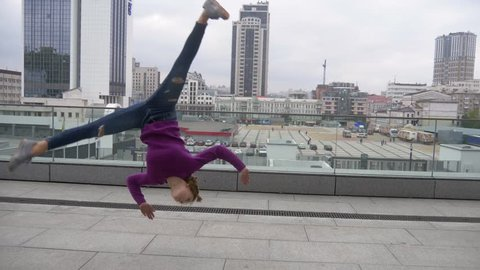 Young attractive woman doing acrobatics with cityscape on background.