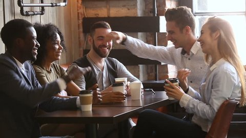 Multi-ethnic friends laughing having fun at meeting in coffeehouse, african and caucasian male buddies giving high five after telling good funny joke, multiracial young people hanging out in cozy bar
