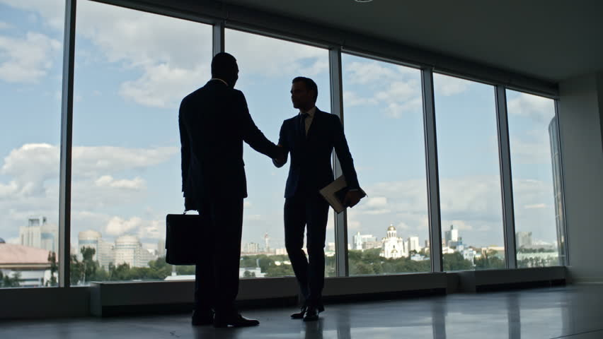 Silhouettes of business partners greeting each other with handshake and walking together through corridor in office building with panoramic windows