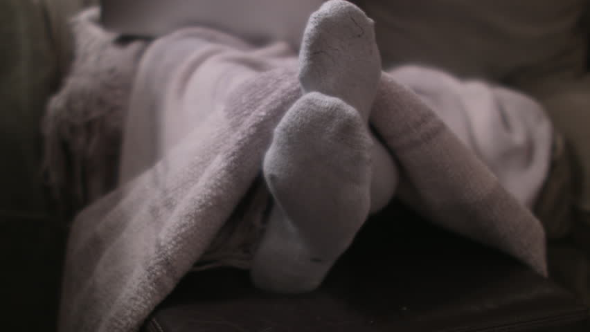Playful feet with white socks under a comfy blanket of a female on a couch. Medium shot. Shallow depth of field. Camera tilting down