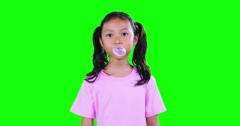 Funny little girl with pigtail hair, chewing gum in the studio with green screen background. Shot in 4k resolution