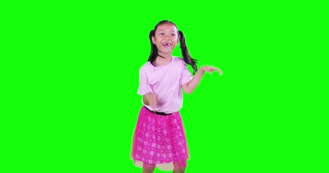 Happy toothless little girl with pigtail hair, dancing in the studio while chewing gum. Shot in 4k resolution with green screen background
