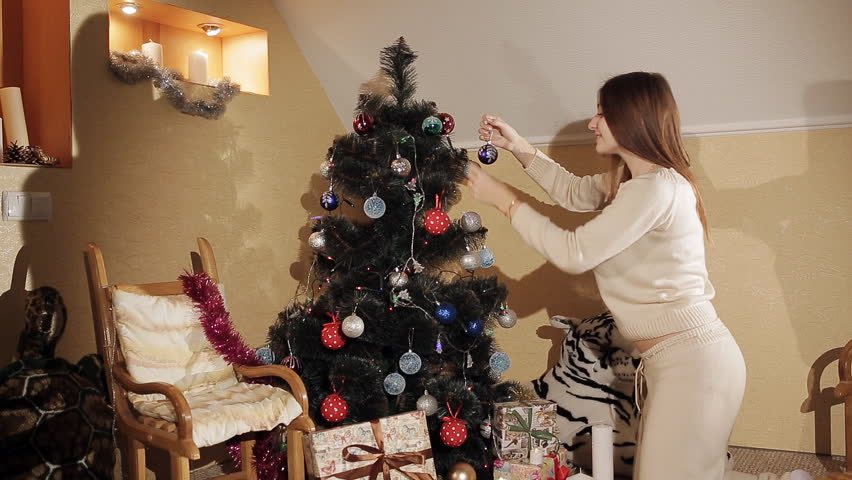 young girl in a knitted suit decorates on a Christmas tree. Cheerful brunette in a New Year's mood. Christmas toys and flickering garlands