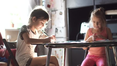 children draw with pencils at home sitting at a table. two little girls sister draw together in the kitchen