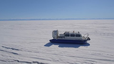 Khivus boat hovercraft tourist entertainment. Baikal lake edge Russia Siberia Frozen. Floats next to Angara river ice Landscape space High rocks. Snow winter sunny day. Best Aerial From above