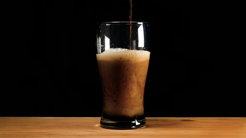 A pint of dark ale beer or stout is poured up.
