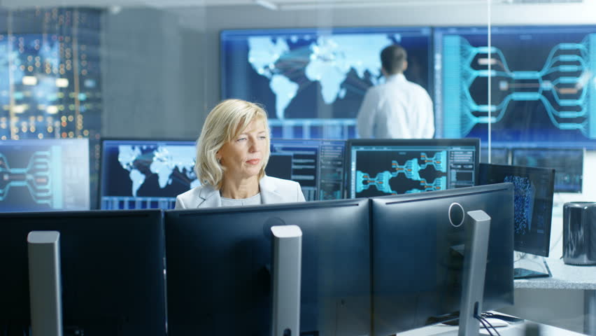 System Monitoring Room Professional Female Operator Observes Correct Functioning of the Facility. In the Background People Working with Interactive Map. Shot on RED EPIC-W 8K Helium Cinema Camera. | Shutterstock HD Video #32307574