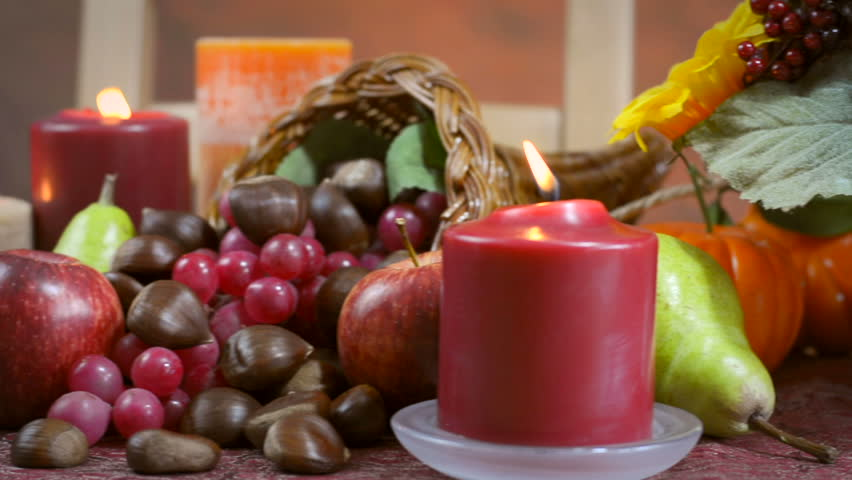 Thanksgiving Fall table setting with Autumn theme chocolate cake, fruit, cornucopia and candles, with lens flare.