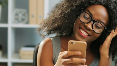 Close up of young happy smiled African American woman chatting on the mobile phone and laughing. Indoor. Portrait